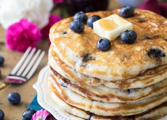 Blueberry pancakes topped with fresh berries and butter