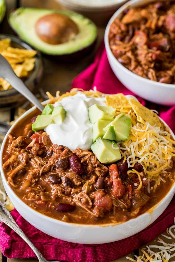 White bowl full of turkey chili with toppings