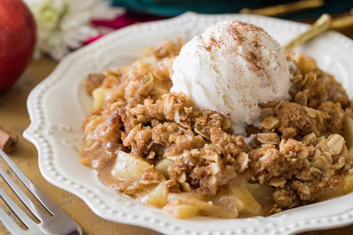 Apple crisp with ice cream on white plate