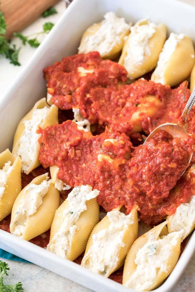 Assembling stuffed shells: stuffed and layering with marinara sauce