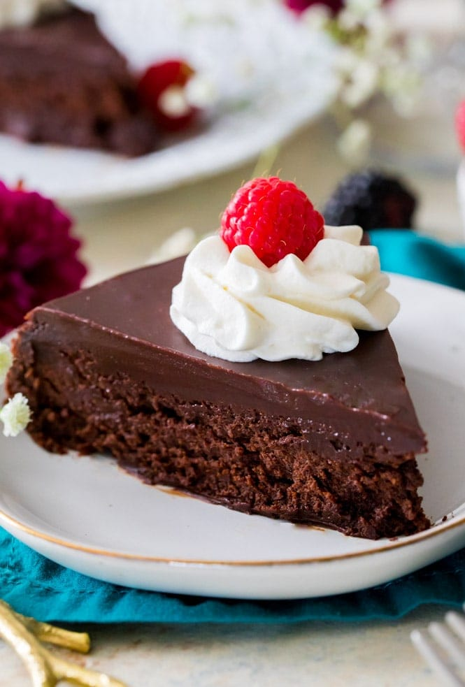Slice of flourless chocolate cake on white plate