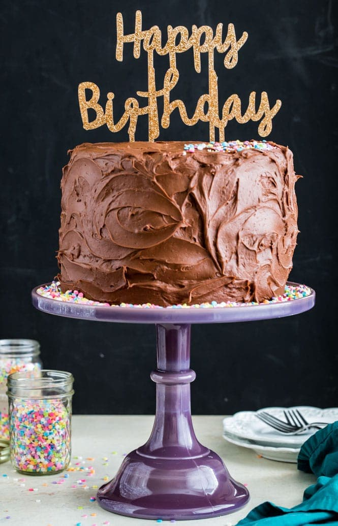 Chocolate frosted birthday cake on a purple cake stand