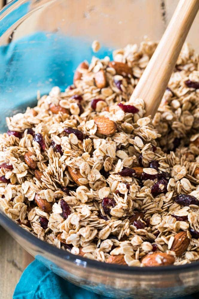 Making granola: stirring together ingredients in large bowl