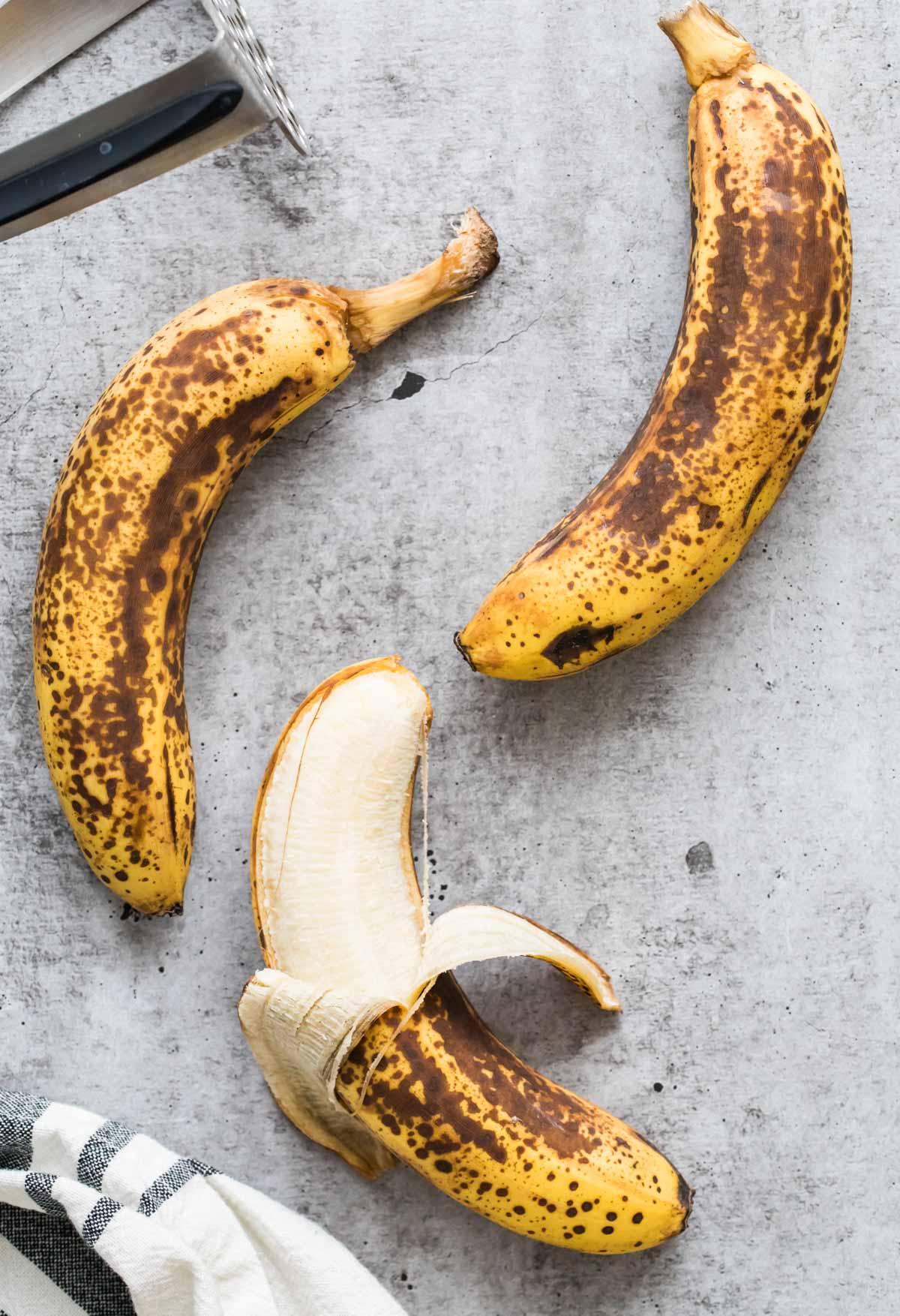 three bananas, one partially unpeeled