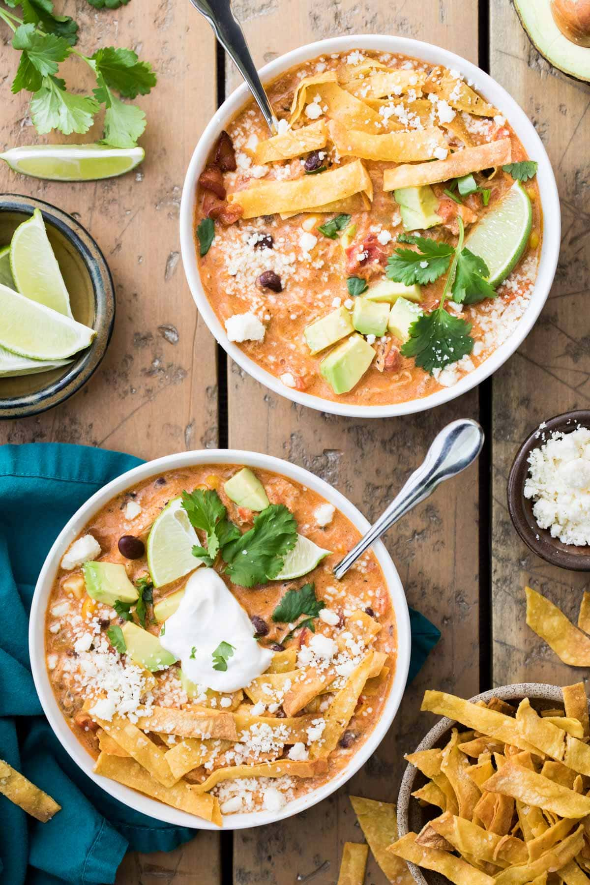 overhead of two bowls of chicken tortilla soup with toppings