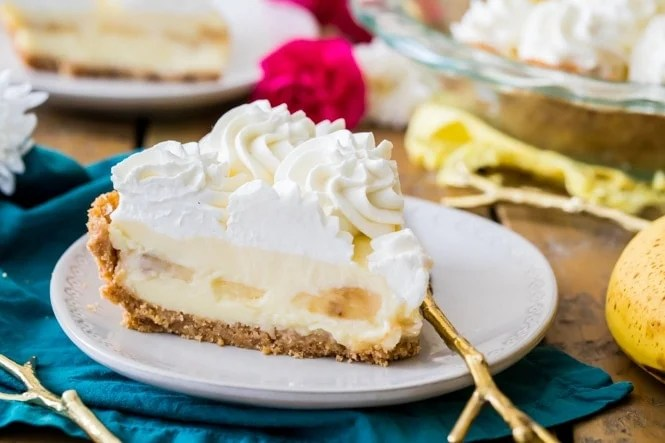 Slice of banana cream pie with whipped cream on plate