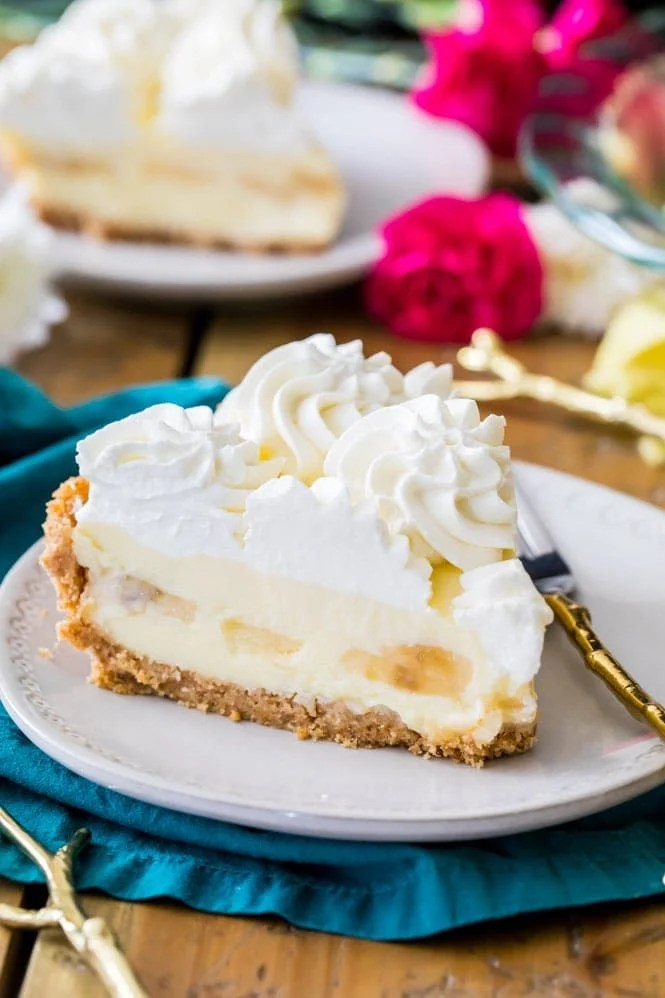 Slice of banana cream pie with whipped cream on white plate