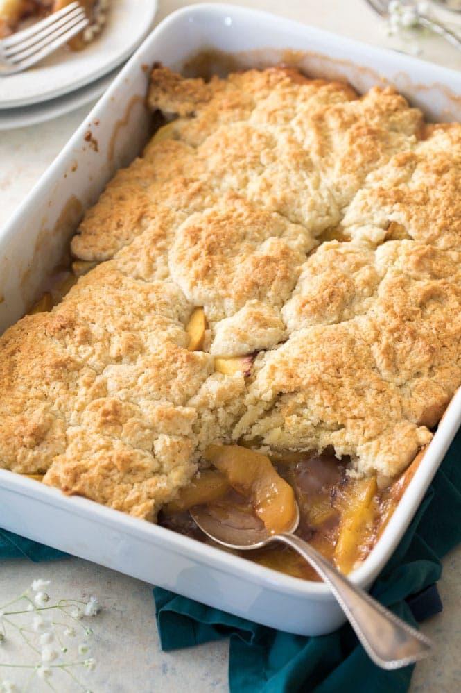 Peach cobbler in white casserole dish