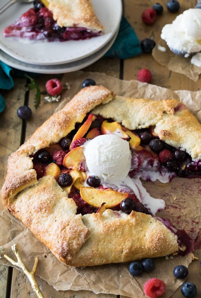 Slicing into a fruit galette that's topped with vanilla ice cream