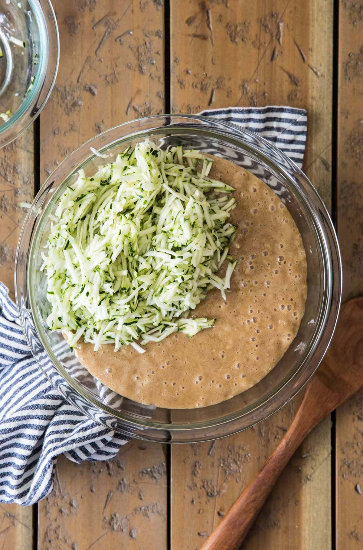 batter with shredded zucchini in glass bowl