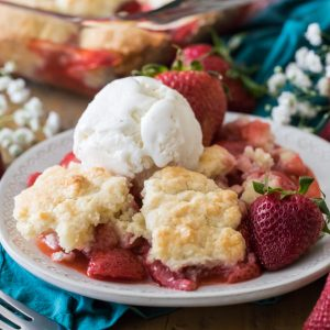 strawberry cobbler with scoop of vanilla icing on a plate