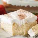 Tres leches cake with fork on white plate