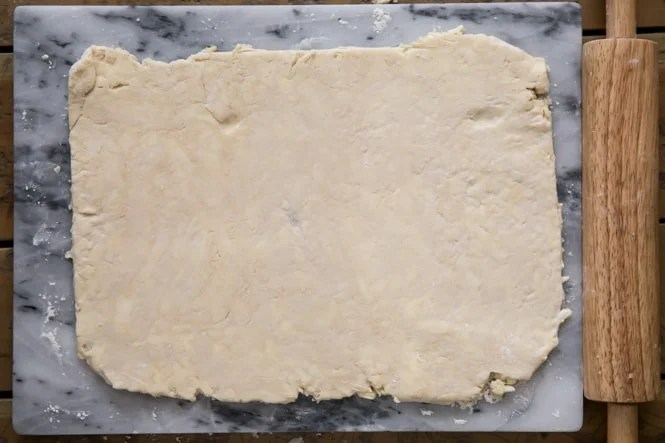 Rolling out puff pastry dough into 8x12 rectangle