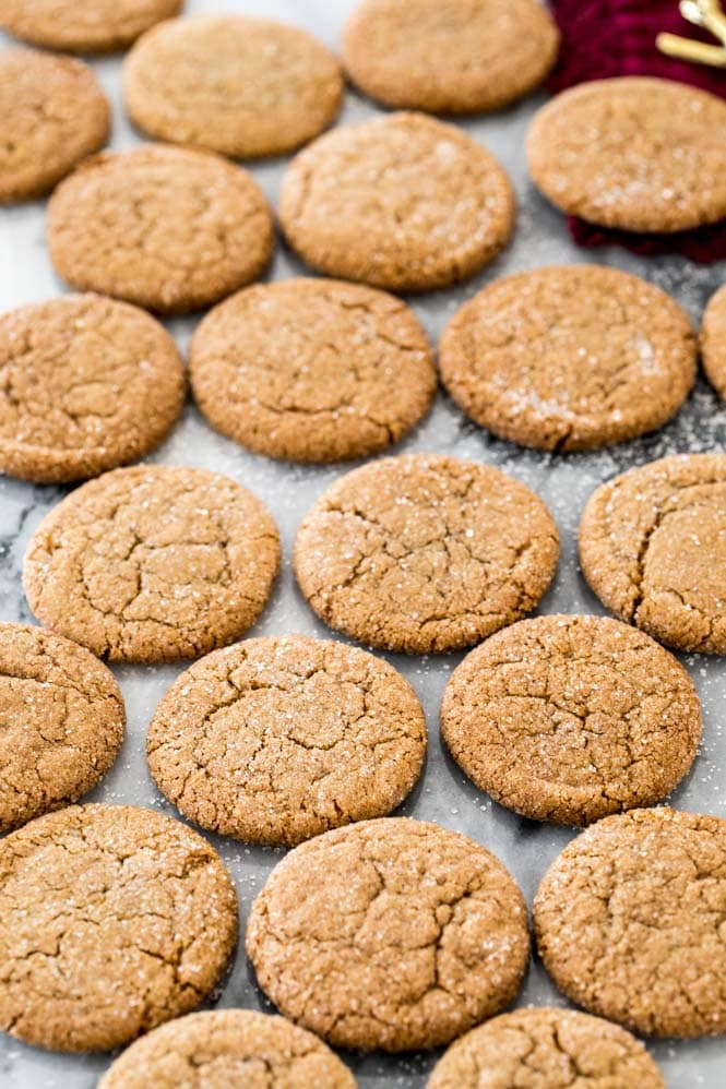 Dozens of gingersnap cookies cooling on marble board