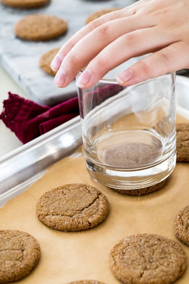 Making gingersnap cookies: Flattening freshly baked cookies by pressing with the bottom of a glass