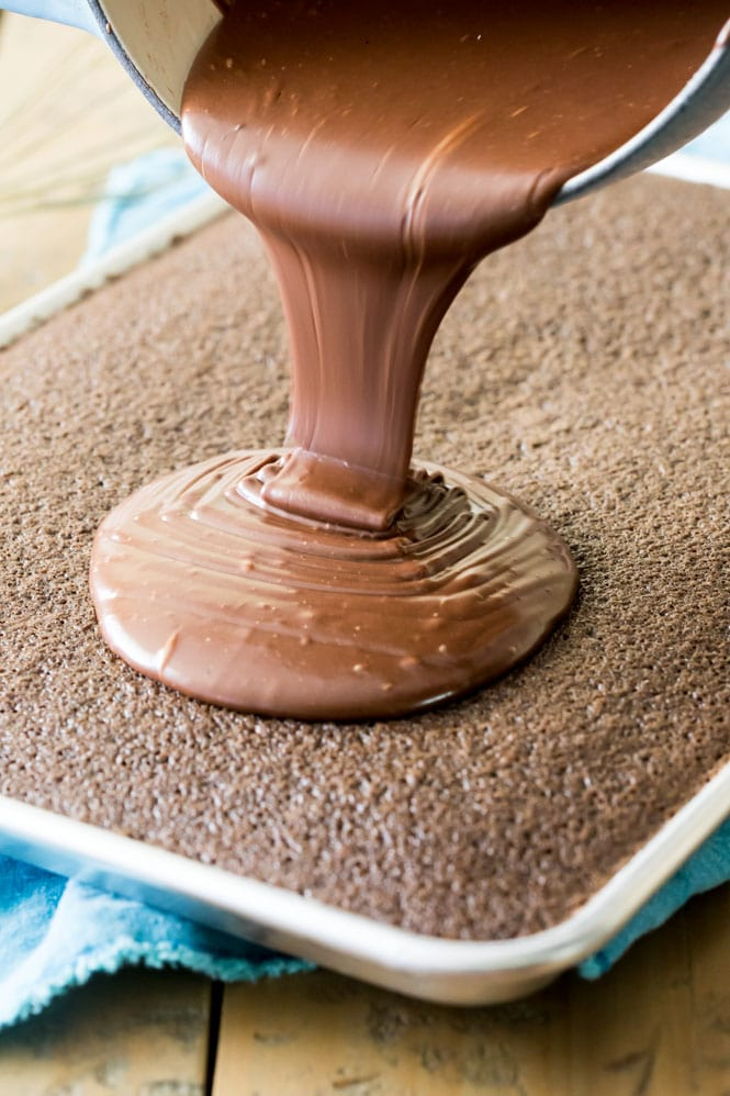 Pouring the chocolate frosting over chocolate sheet cake