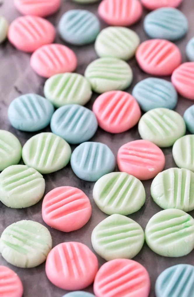 Pink, blue, and green cream cheese mints on a marble board