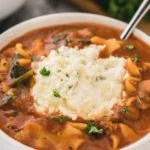 Lasagna soup topped with ricotta cheese mixture in white bowl