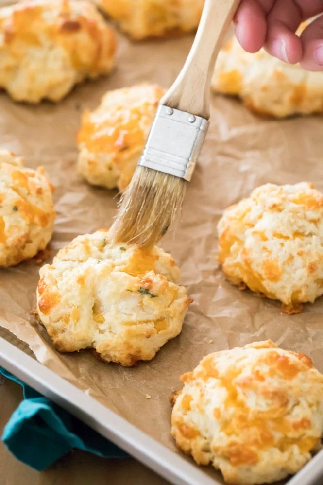 Brushing butter over a freshly baked garlic cheese drop biscuit on a baking sheet