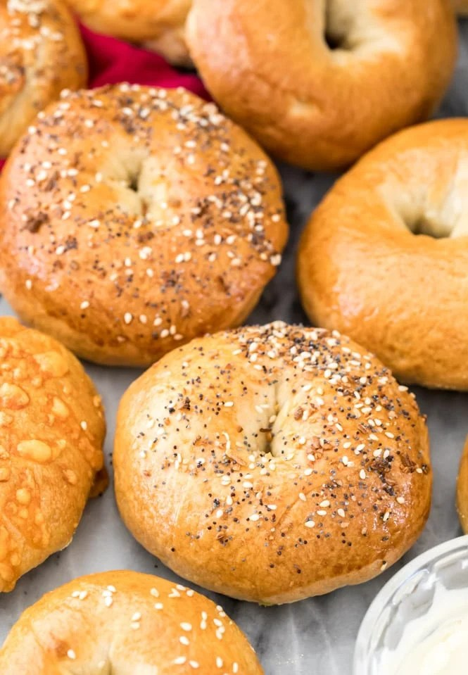 a variety of bagels on marble next to a bowl of cream cheese