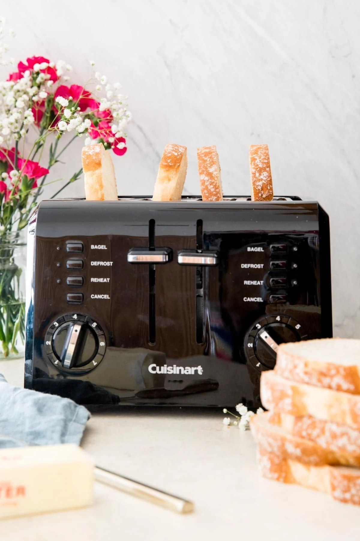 4 pieces of toast in a black toaster with pink and white flowers in the background
