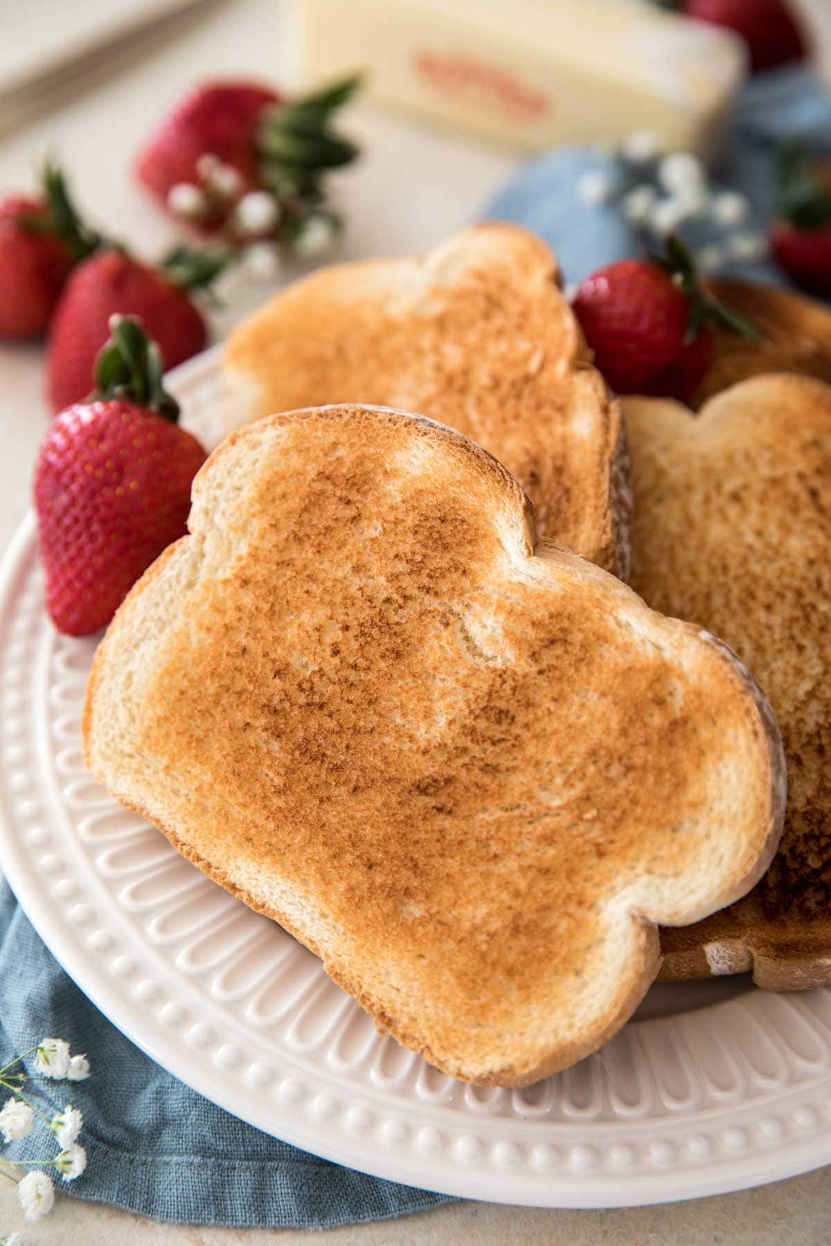 Toast on a white plate with strawberries in the background