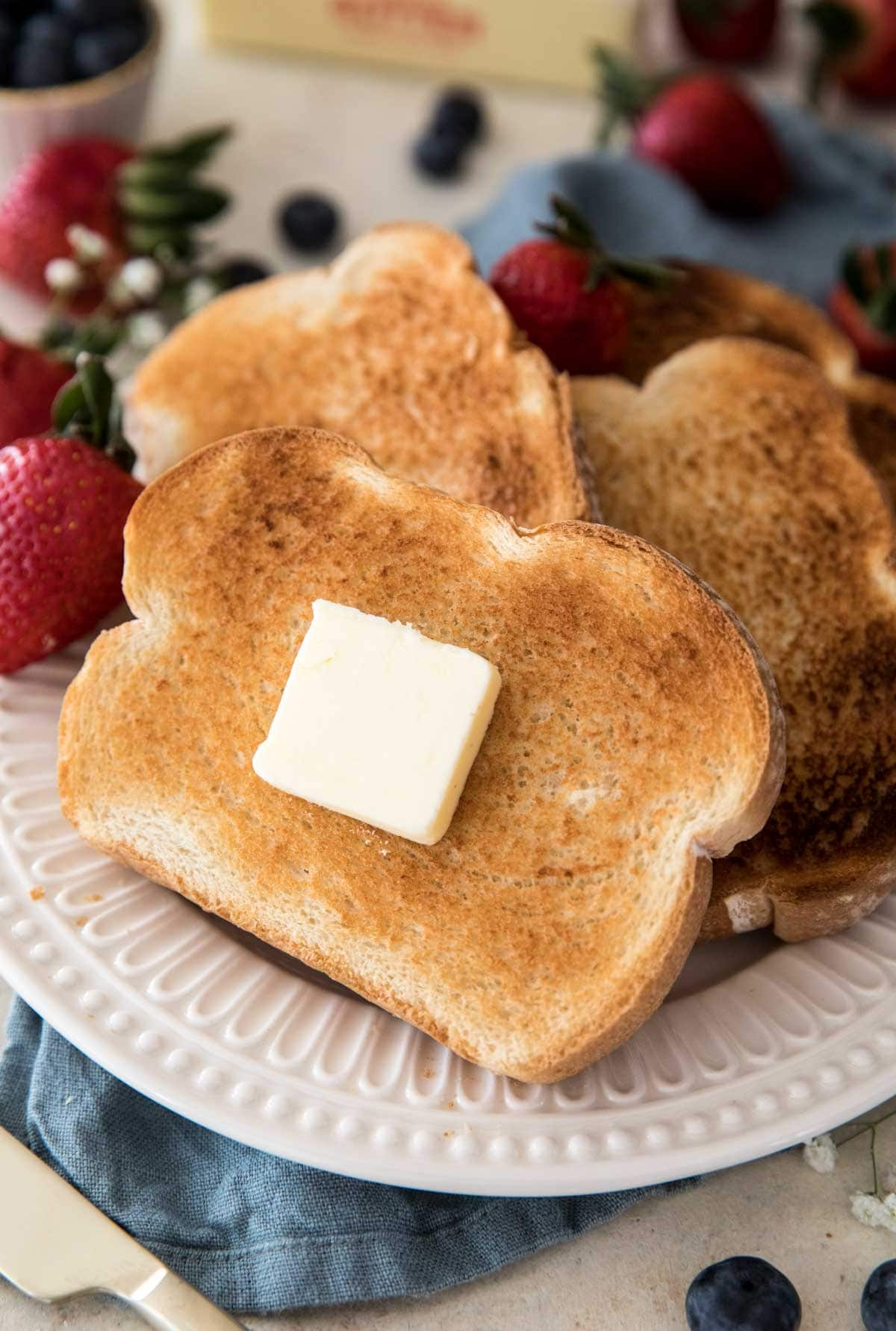 Toast with butter on a white plate surrouned by strawberries