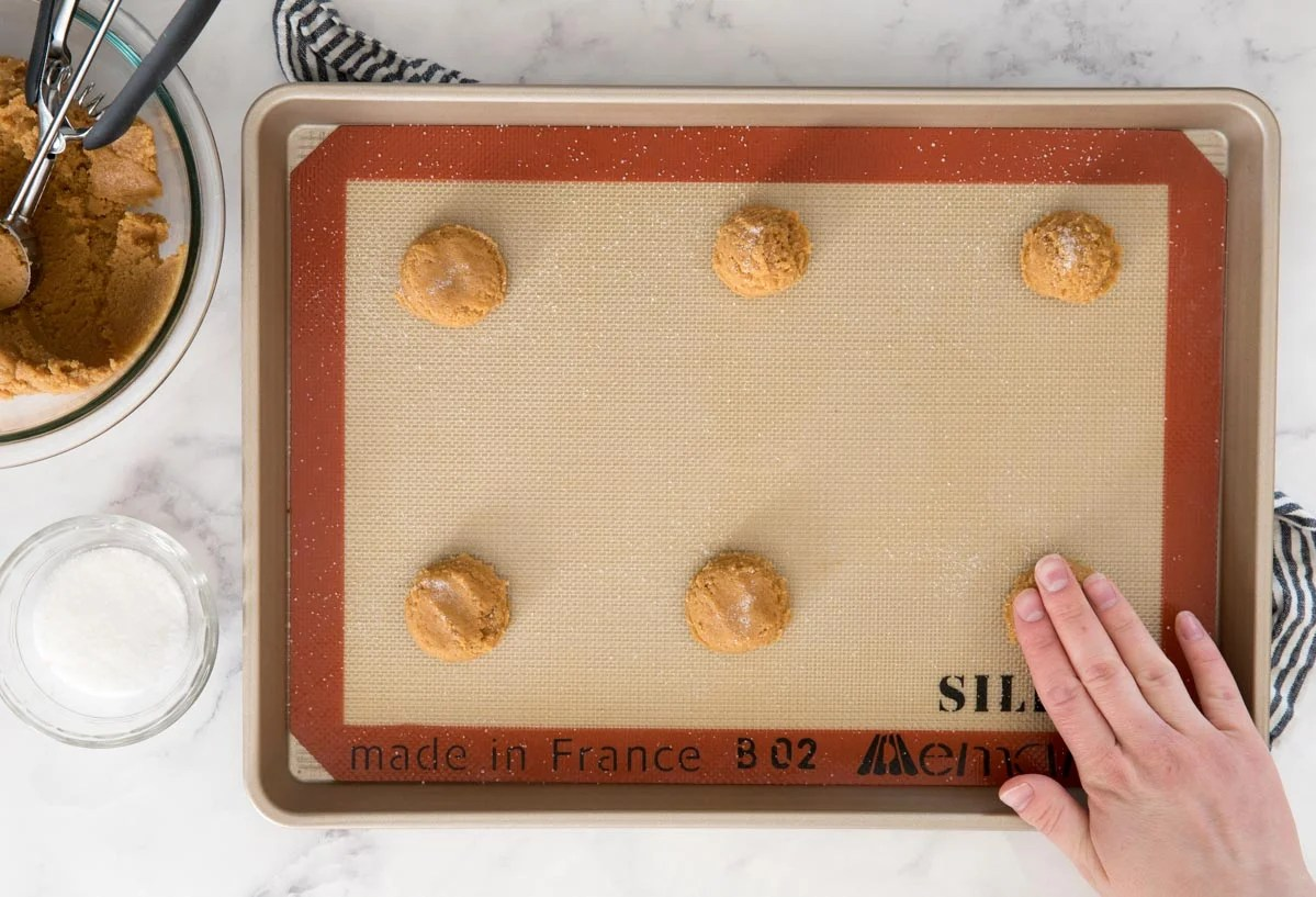Cookie dough balls on a baking sheet being flattened with clean fingers