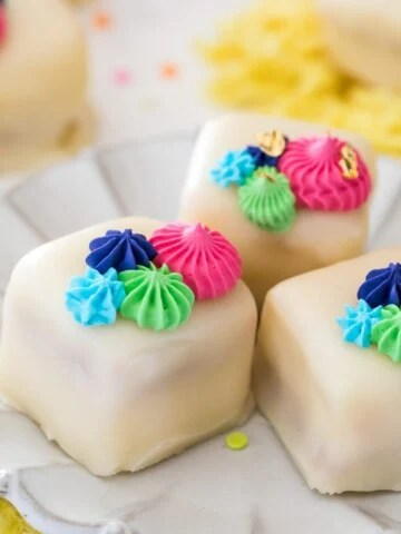 Petit fours on white plate with colorful frosting
