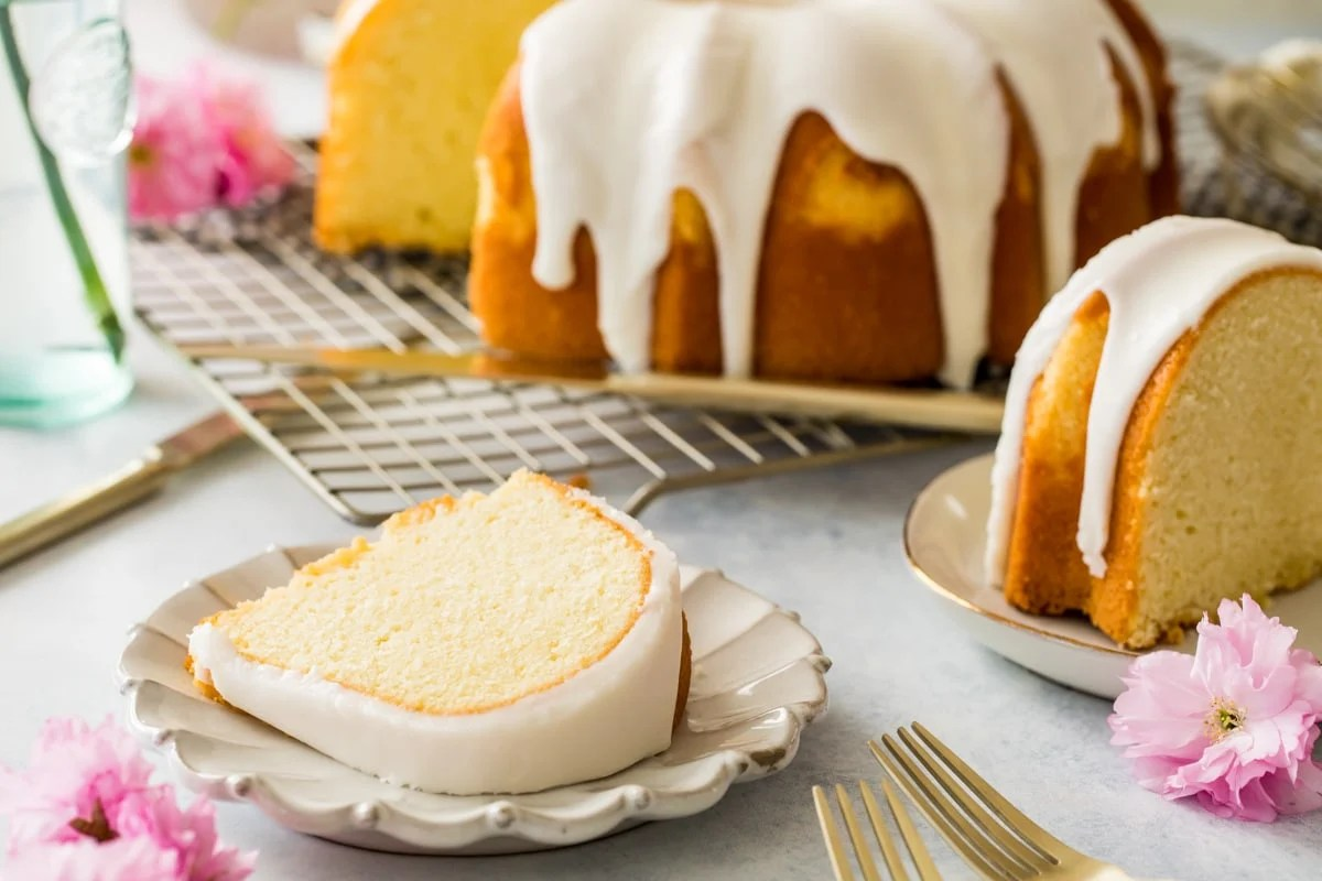 slice of bundt cake on white plate with cake in background