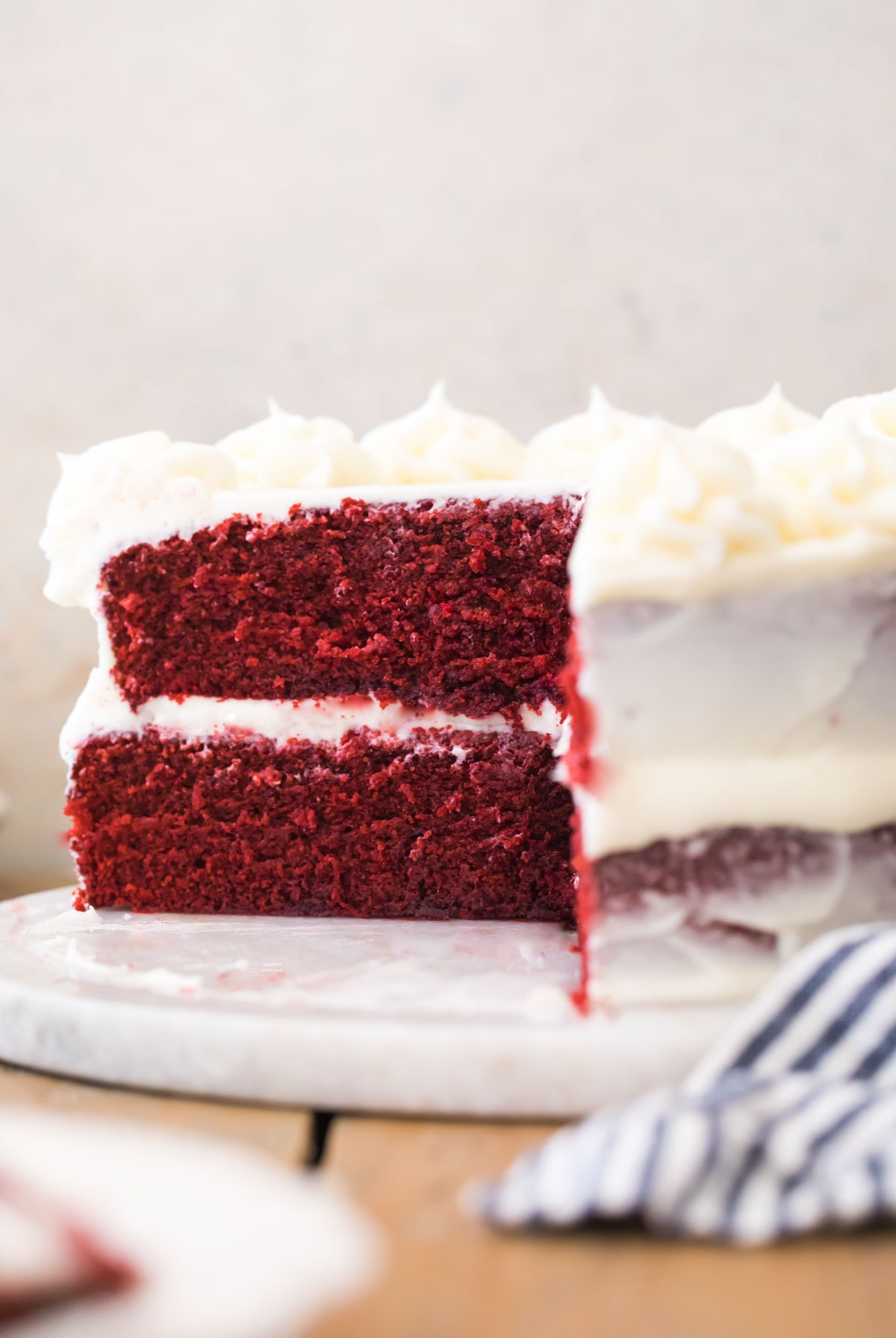 Red Velvet cake with slice missing on white marble