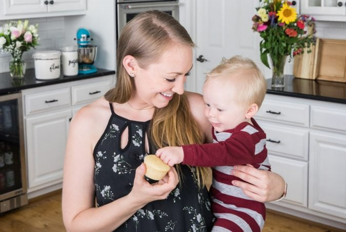 the author holding a cupcake with her baby
