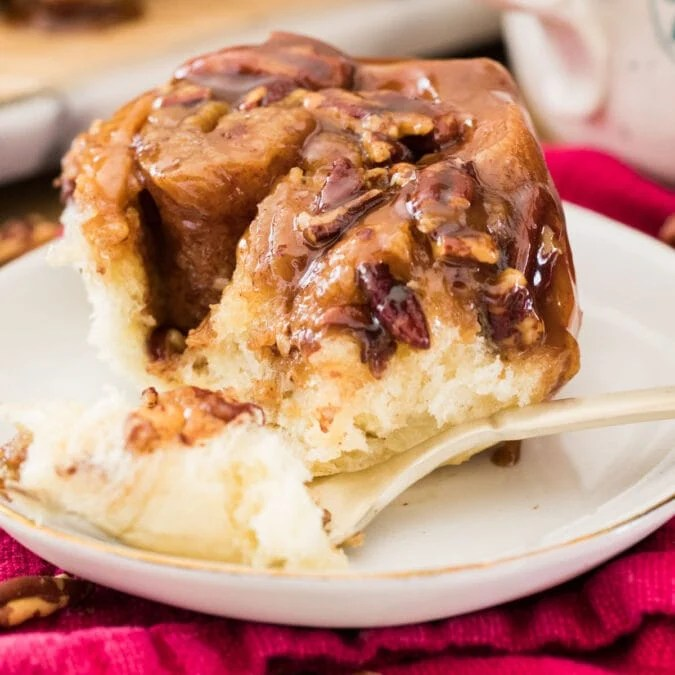 Sticky bun on white plate with fork