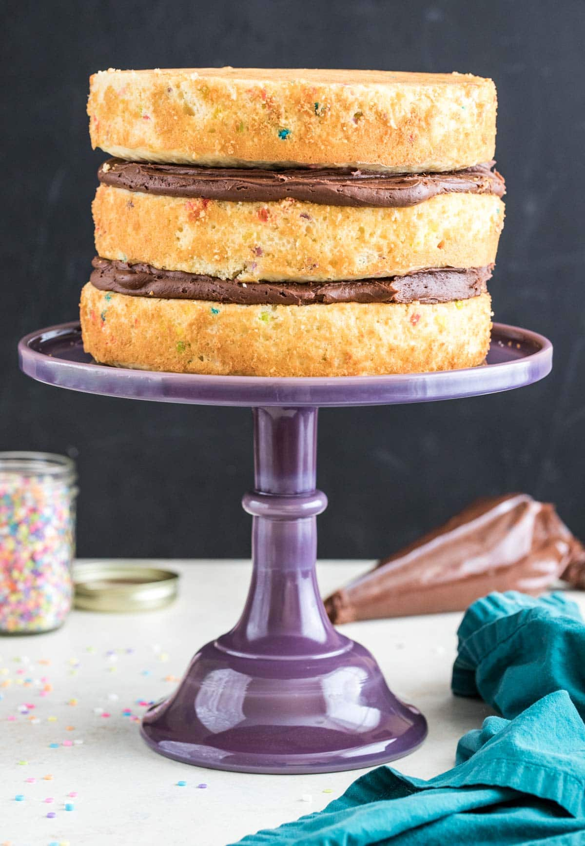Purple glss cake stand with three layer cake on top