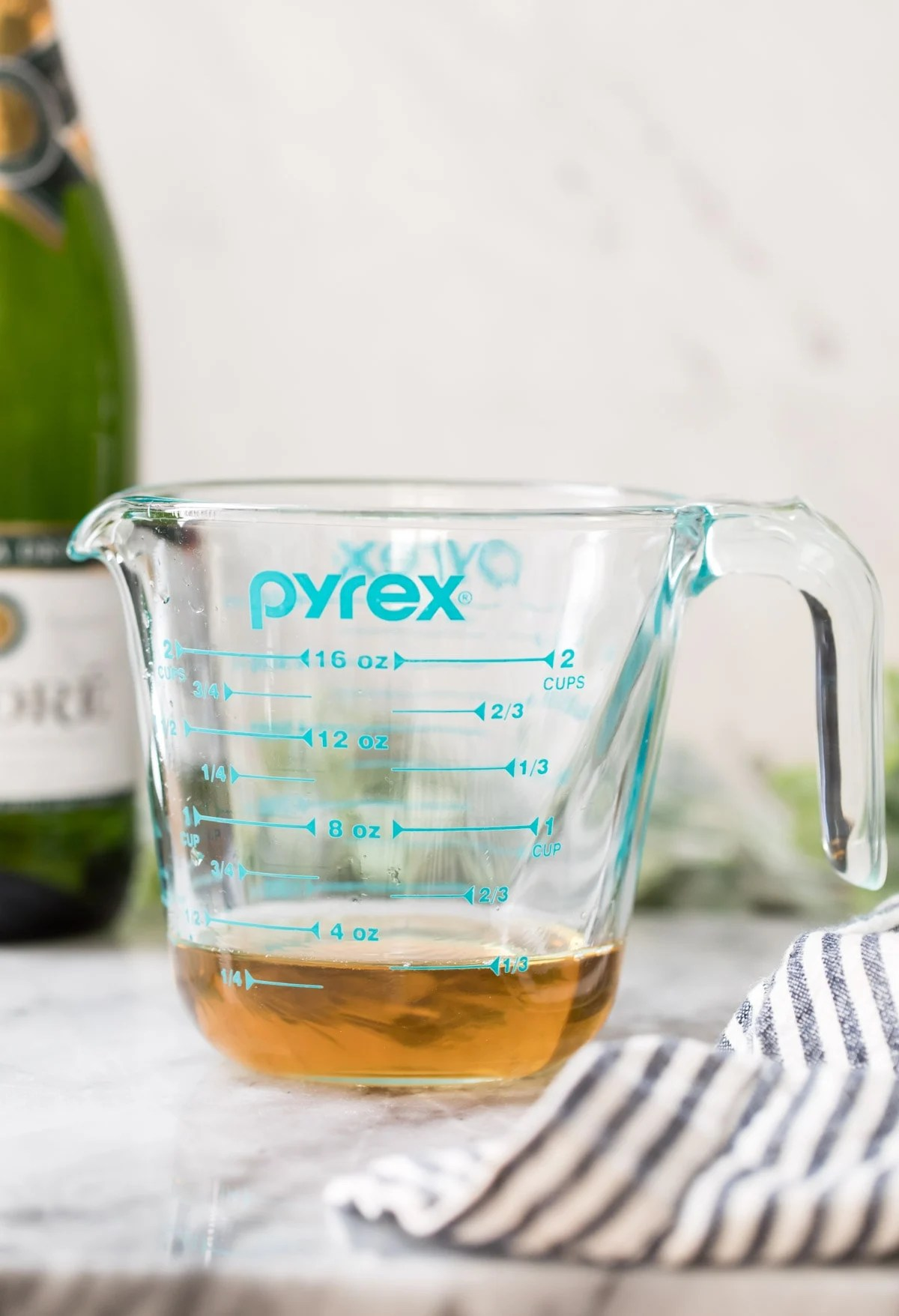 champagne that has been reduced in a blue measuring cup