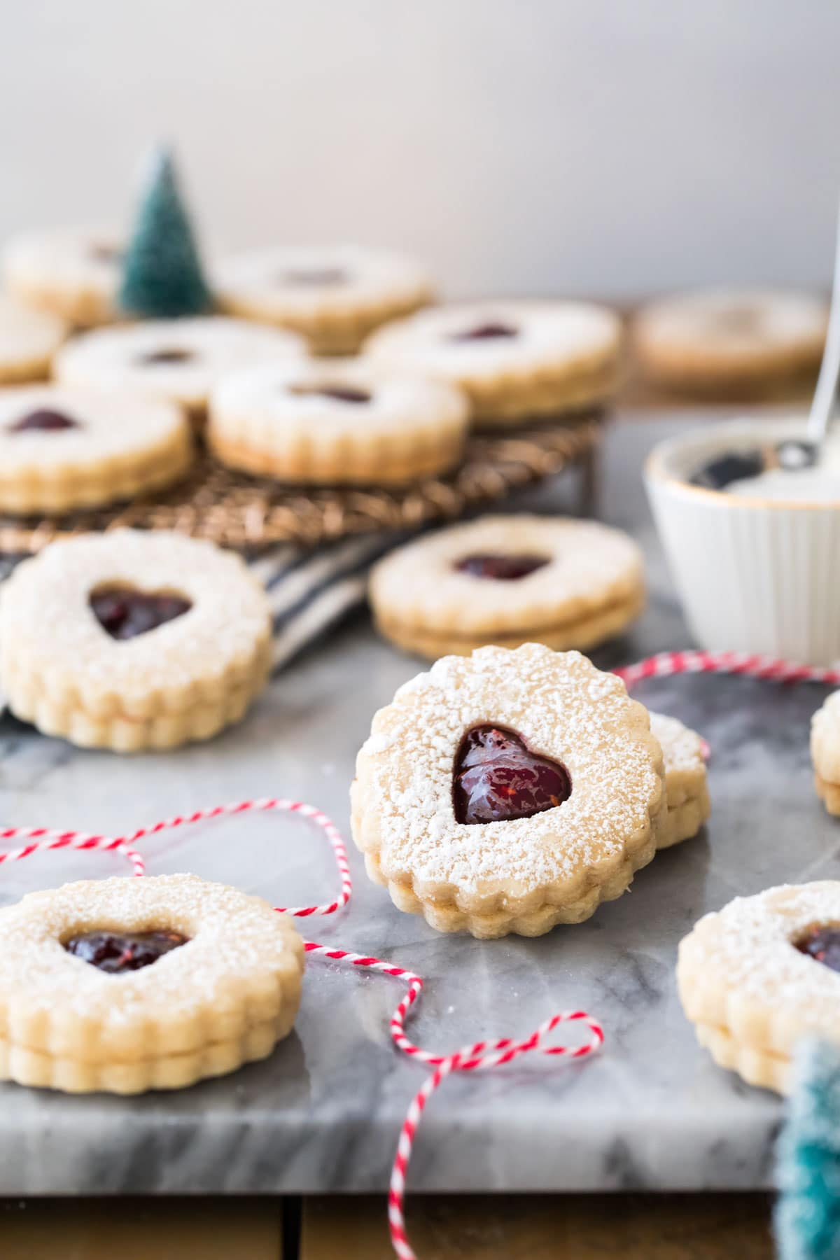 Linzer cookies on marble with red bakers twine