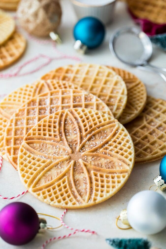 Pizzelle arranged on white board surrounded by ornaments