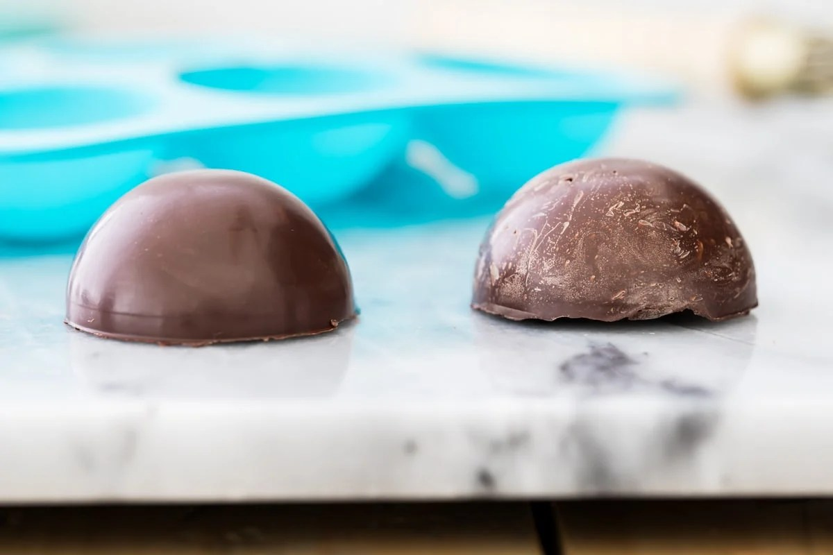 shiny tempered chocolate half sphere on left, chalky, white-streaked un-tempered chocolate half sphere on right