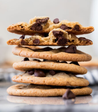 stack of thin chocolate chip cookies, white background