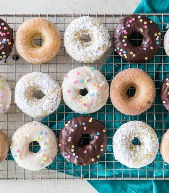 overhead of baked donuts with different toppings (chocolate frosting, cinnamon sugar, white frosting)