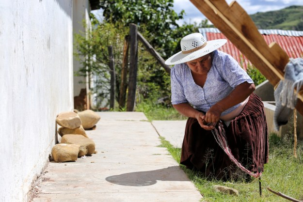 Aramasi weaving wool in the sun to better see the colours, Lake Titicaca