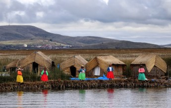 Women in flashy coloured dresses waiting to welcome travellers to their island Lake Titicaca, Peru and Bolivia