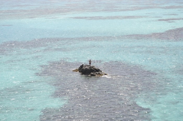A solitary man on a rock island off the coast of Providencia Island, Colombia