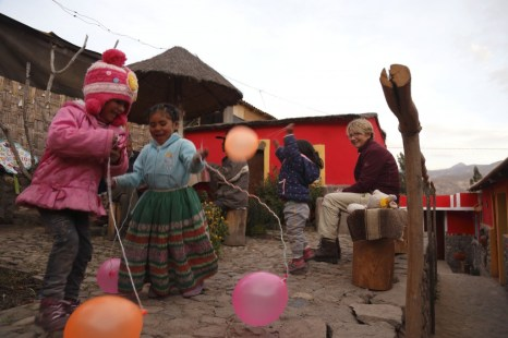 Local children play in a house courtyard in Coporaque, Peru