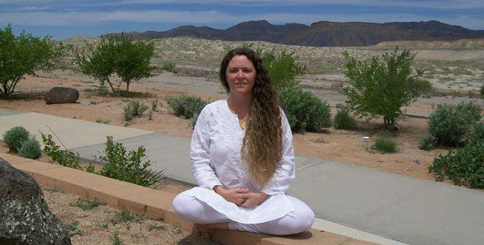 Sumati Govinda sitting meditatively in the desert