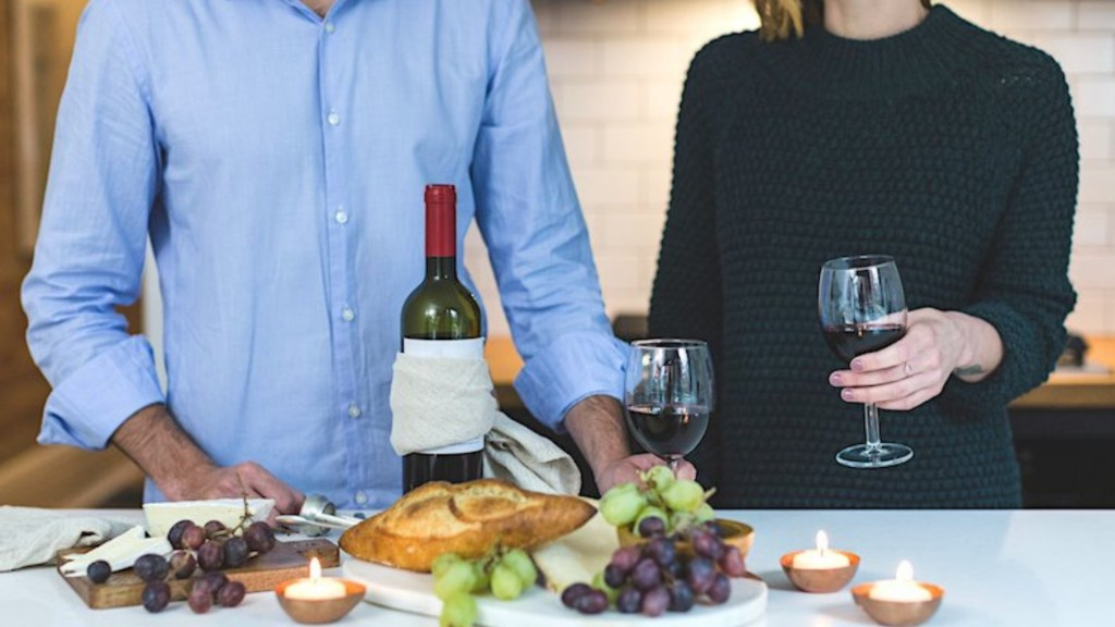 Mid-shot of man and woman standing at kitchen marble island with wine and cheese.