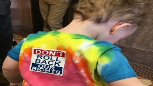 """Young child wearing a tie-dye shirt with a """"Don't Roll Back Our Rights"""" sticker on the back."""