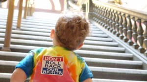 "Young child looking up the Capitol Rotunda staircase. Child is wearing a tie-dye shirt with a ""Don't Roll Back Our Rights"" sticker on the back."