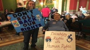 "Tom Osborn and Mike Mayer holding up signs that say ""Don't Roll Back Our Rights"" and "" Disability Rights are Human Rights"" during Rally Day 2017"