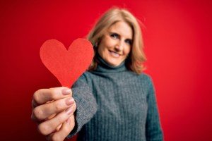woman holding red paper heart with a happy face